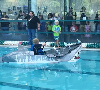 Cardboard Boat Race participant sailing in Summit Aquatic Center's pool